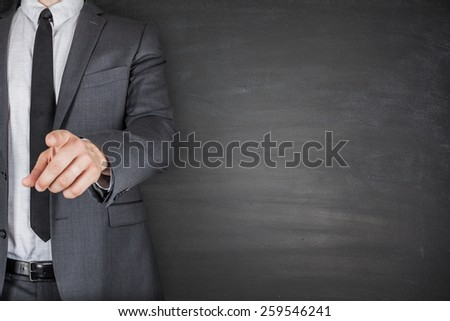 Businessman with suit and tie front of Blackboard - stock photo