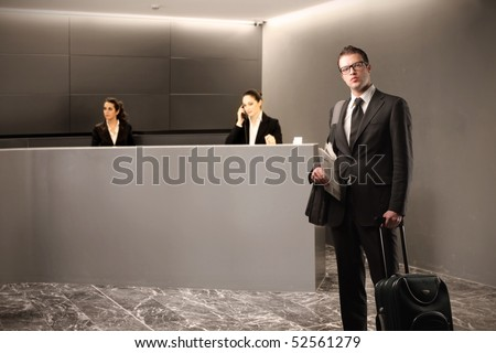 Businessman with suitcase and two businesswomen at the reception desk on the background - stock photo