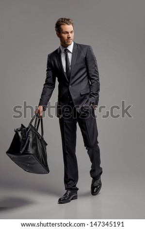Businessman with suitcase. Full length of confident young businessmen in carrying a suitcase while isolated on grey - stock photo