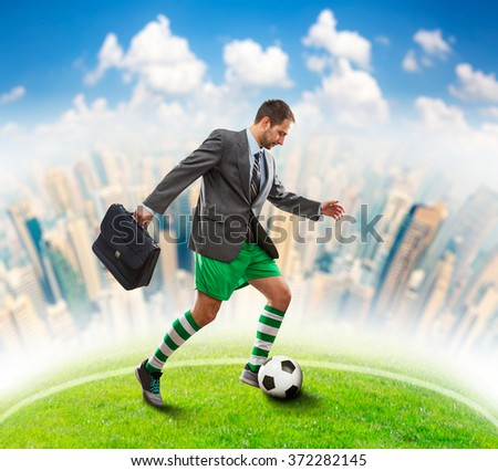Businessman with suitcase in sportwear playing football in the town - stock photo