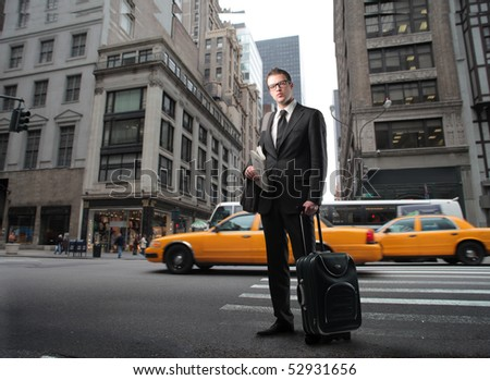Businessman with suitcase standing on a city street - stock photo