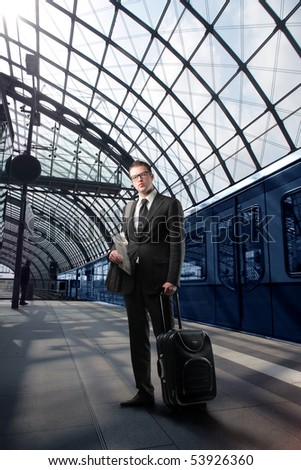 Businessman with suitcase standing on a platform of a train station - stock photo