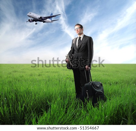 Businessman with suitcase standing on green meadow with airplane on the background - stock photo