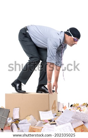 Businessman with swimming gear ready to dive to a pool of office papers - stock photo