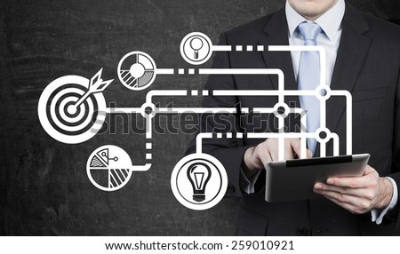 businessman with tablet and drawing business icons - stock photo