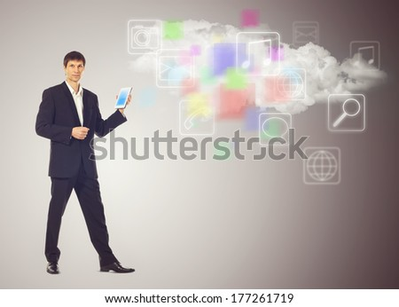 Businessman with tablet and the cloud with applications icons on grey background - stock photo