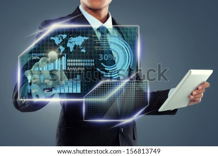 Businessman with tablet computer working on screen over virtual background - stock photo