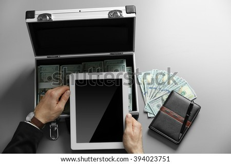 Businessman with tablet, notebook and case full of money