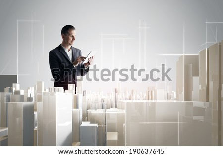 Businessman with tablet PC working with a modern city project - stock photo