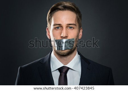 Businessman with tape on his mouth - stock photo