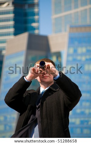 Businessman with telescope looking to the future - stock photo