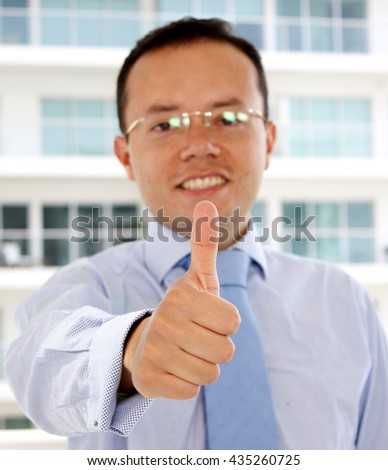 Businessman With Thumb Up, Standing Outside a Modern Office Building - stock photo