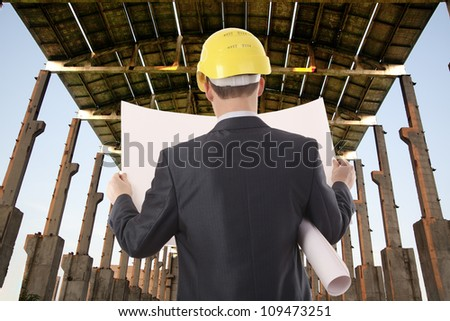 Businessman with time schedule under roof  building - stock photo