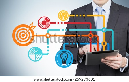 businessman with touch pad and drawing business icons - stock photo