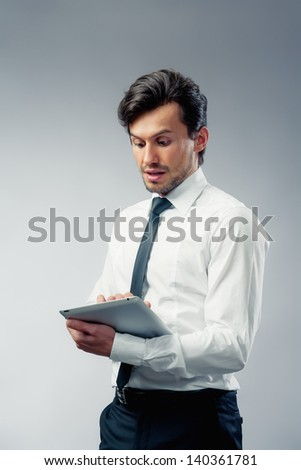 businessman with touch pad grey background