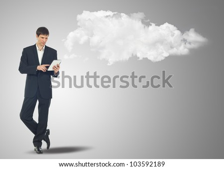 Businessman with touch screen Internet Tablet and the clouds - stock photo