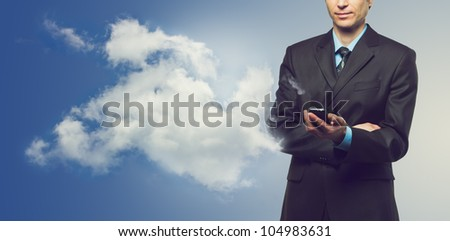 Businessman with touch screen phone and the cloud on blue background - stock photo