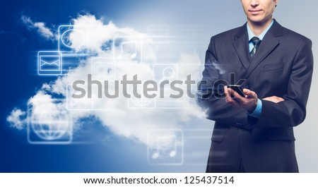 Businessman with touch screen phone and the cloud with icons on blue background