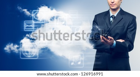 Businessman with touch screen phone and the cloud with icons on blue background - stock photo