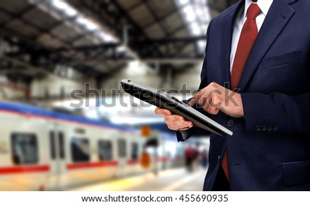 Businessman with touchpad at train station - stock photo