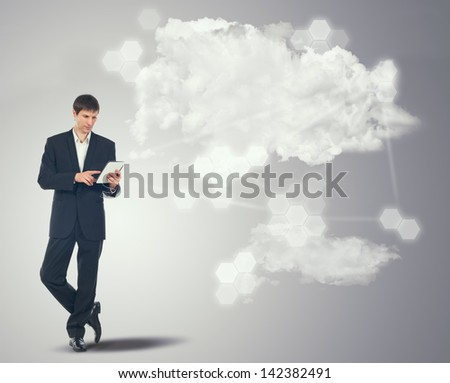 Businessman with touchscreen internet tablet and the clouds on grey background - stock photo