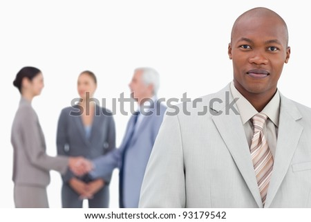Businessman with trading partners behind him against a white background - stock photo