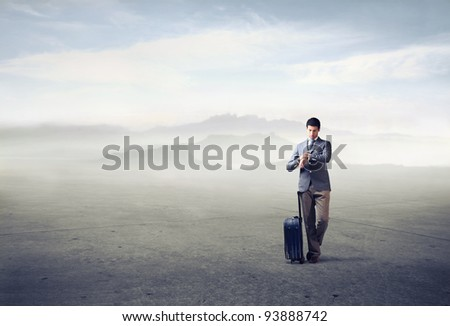 Businessman with trolley case looking at his watch - stock photo