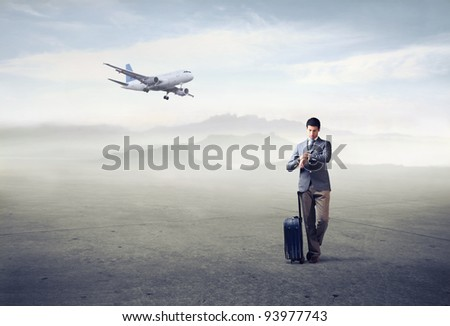 Businessman with trolley case looking at his watch with airplane in the background