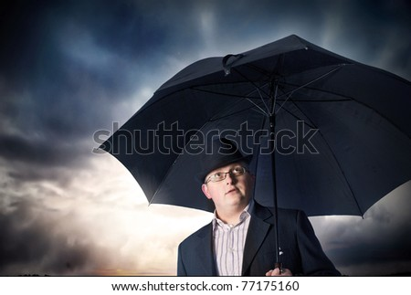 Businessman with umbrella and storm clouds background
