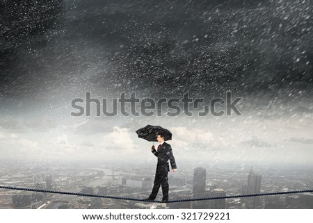 Businessman with umbrella balancing on rope high on sky - stock photo