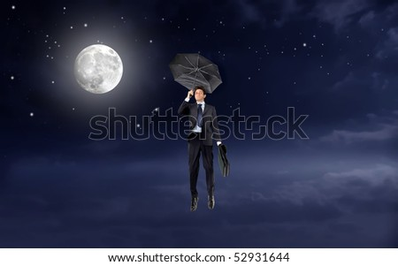 Businessman with umbrella flying in the sky with full moon - stock photo