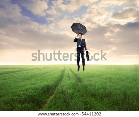 Businessman with umbrella flying over a green meadow