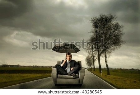 businessman with umbrella in a stormy landscape - stock photo
