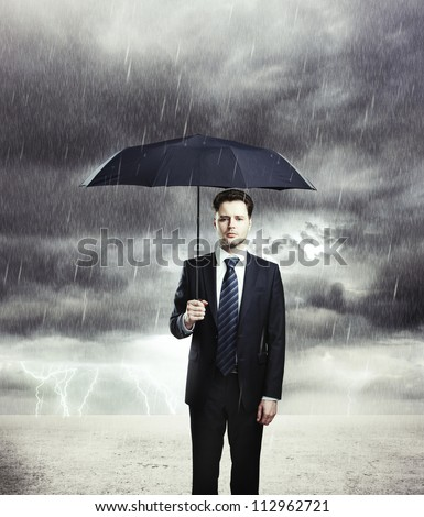 Businessman with umbrella in rain