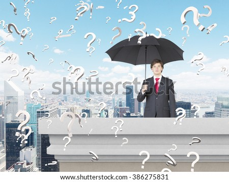 Businessman with umbrella on balcony. Blue sky at background, question marks everywhere. Paris view. Concept of problem rain