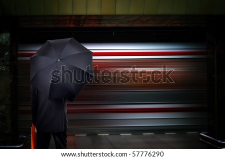 Businessman with umbrella on train station.