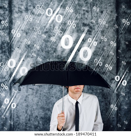 Businessman with umbrella protecting himself from percentage rain. Concept of share profits; credit; money loan interest; finance and economy.