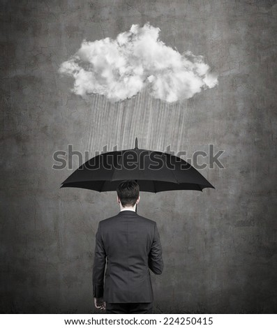 Businessman with umbrella protecting himself from the storm. A concept of protection from recession or economic crisis. - stock photo