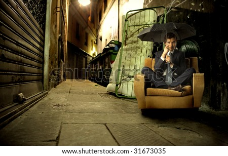 businessman with umbrella sitting on armchair in a city street - stock photo