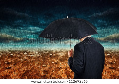 Businessman with umbrella standing in the desert during the rain.