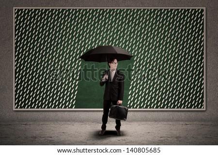 Businessman with umbrella under the rain on blackboard - stock photo