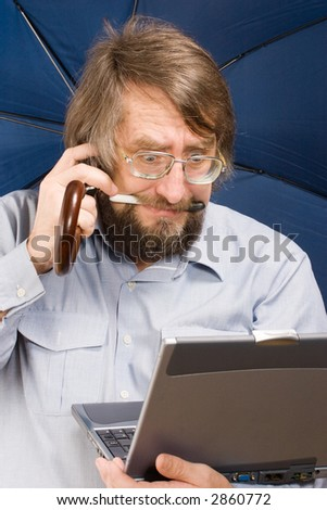 businessman with very surprised face in glasses with notebook, phone mobile, umbrella in his hands and pen in his teeth - stock photo