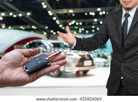 Businessman with welcoming gesture and Man hand holding and giving a car key remote on photo blurred of car, transportation and ownership concept