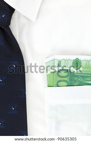 Businessman with white shirt with blue tie and money in his pocket. Salary or bribe? - stock photo