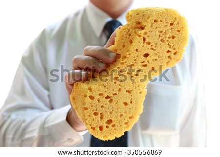 businessman with yellow sponge ,hands hold sponge for washing car in car care business shop, Man's handing holding a large sponge for cleaning. - stock photo