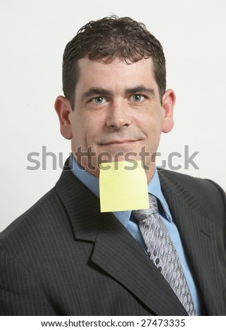 Businessman with yellow sticky note on face - stock photo