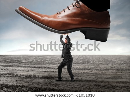 Businessman withstanding a shoe trying to squeeze him - stock photo