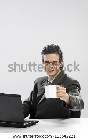 Businessman working at a laptop and holding a coffee cup - stock photo