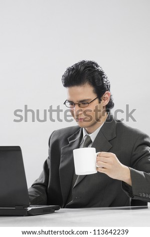 Businessman working at a laptop and holding a coffee cup