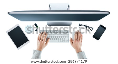 Businessman working at computer at office desk, hands close up top view, white background - stock photo